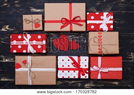 Top view of two red greeting card encircled with gift boxes isolated over flat layout. Boxes tied with ribbons
