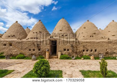 Photo is taken in Harran Sanliurfa Turkey. This is the photo of the typical Harran house. Houses is made of mudbrick. Door and small windows can be seen too. Conic shaped and mudbrick and conic roofs are special to Harran area. Some special tool are hangi