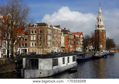 AMSTERDAM, NETHERLANDS - JANUARY 2, 2017: Vessels in a canal against the tower Montelbaanstoren. The tower was built in 1516 and extended to its current, decorative form in 1606