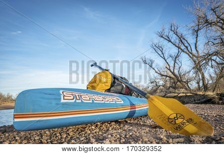 KERSEY, CO, USA - JANUARY 29, 2017: Winter stand up expedition paddling on the South Platte RIver in eastern Colorado - All Star racing paddleboard by Starboard, a Werner paddle during a rest stop.