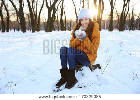 Beautiful young woman playing with snow outdoors on winter day