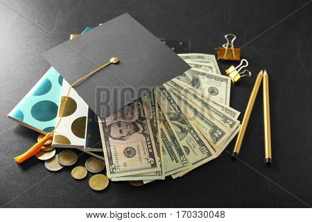 School supplies, graduation hat, dollar banknotes and coins on blackboard. Pocket money concept