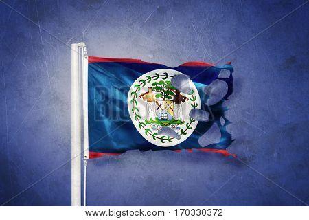 Torn flag of Belize flying against grunge background.