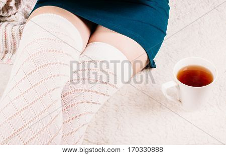 Beautiful legs of the young girl in white stockings on a white background carpet and a cup of black tea standing next to them