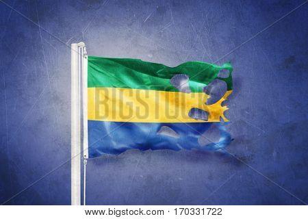 Torn flag of Gabon flying against grunge background.