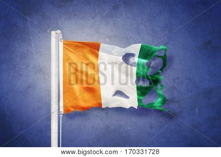 Torn flag of Cote d'Ivoire flying against grunge background.