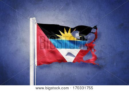Torn flag of Antigua and Barbuda flying against grunge background.