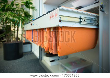 old and used orange paper File Folders in a metal filing cabinet.Cupboard with suspension files poster