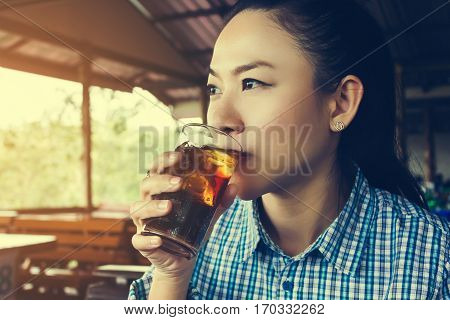 Asian women drink soda or soft drink in sunny day at restaurant glass of coca cola with ice in women hand