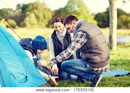 camping, tourism, hike, family and people concept - happy parents and son setting up tent outdoors