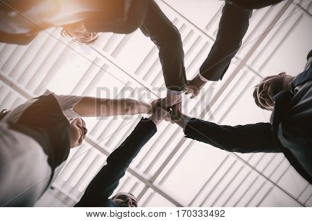 Low angle view of happy businesspeople giving high five to each other in office premises