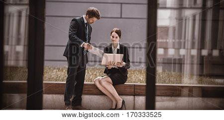 Businessman showing digital tablet to colleague in office premises