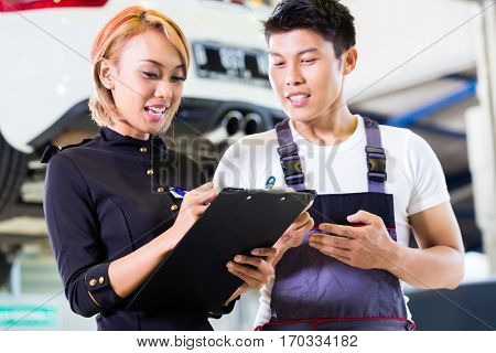Asian Car mechanic and manager assigning tasks in auto workshop