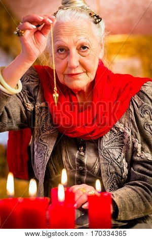 Fortuneteller dowsing with pendulum looking into the future