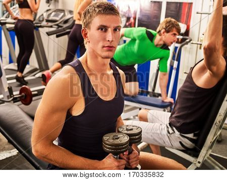 Friends in gym workout with fitness equipment. Man holding dumbbell workout at gym. Group people working strong muscular on simulator his body and running on treadmill at gym on background.