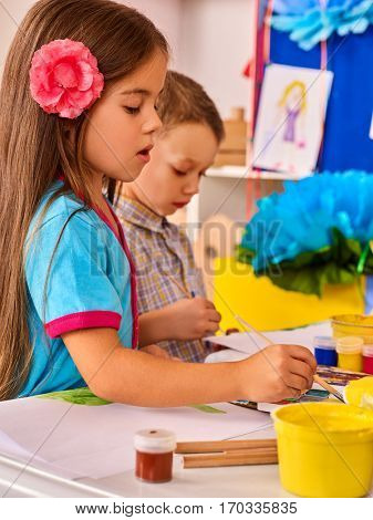 Small students painting in art school class. Child drawing by paints on table. Girl and boy together. Portrait of little girl in kindergarten. Drawing education develops creative abilities of children