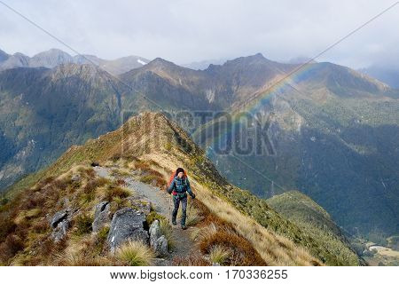 A Smiling Woman Hiker and a Rainbow on The Kepler Track.  Fjordland National Park, Southern Alps, New Zealand.