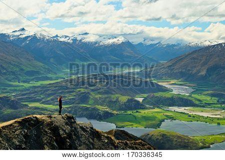 A Woman Hiker and Summit Views on Roys Peak.  Wanaka, Southern Alps, New Zealand.