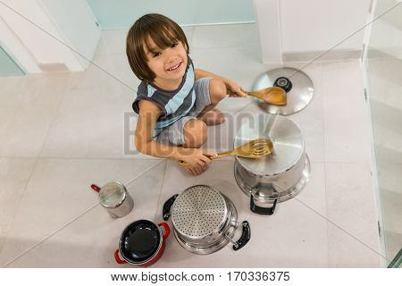 Happy kid at home playing with dishes as music instruments and drums