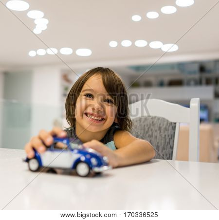 Happy kid at home with oldtimer car toy playing