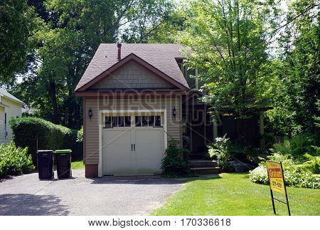 HARBOR SPRINGS, MICHIGAN / UNITED STATES - AUGUST 4, 2016: A small home with an attached one-car garage is for sale in Harbor Springs, Michigan.