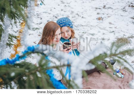 The girls sit near trees in winter on snow and drinking tea from a cup