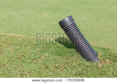 The black plastic pipe tip under the meadow in green golf course for water draining. construction & infrastructure spare part.