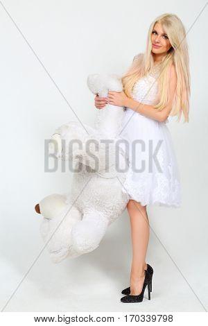Beautiful woman in white dress raises big toy bear in white studio