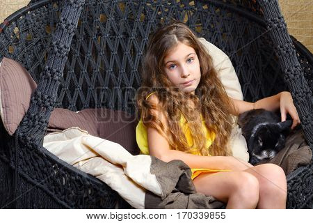 Girl in yellow poses with funny rabbit on black hanging sofa in room