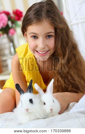 Girl sits with two funny fluffy cubs of rabbit on bed and smiles in bedroom
