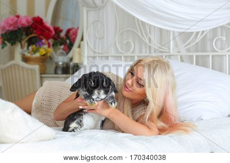 Pretty blonde lies on white bed and holds fluffy black rabbit in room