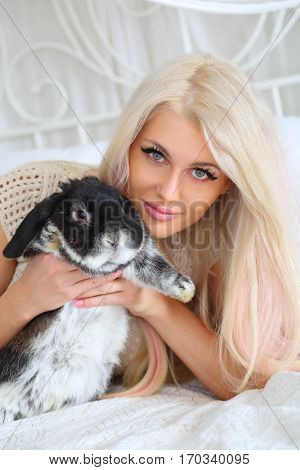 Pretty girl lies on white bed and holds fluffy black rabbit in room