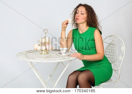 Pretty woman in green holds marshmallow souffle at table in white studio