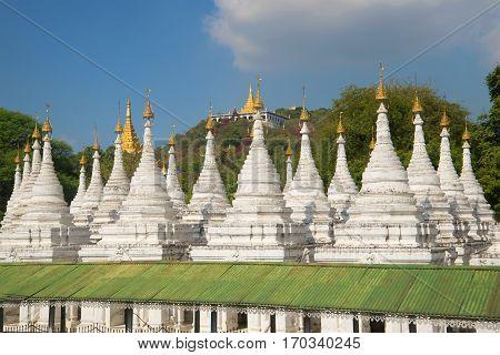 Stupas of the Sandamuni pagoda on the background of the sacred hill. Mandalay, Myanmar