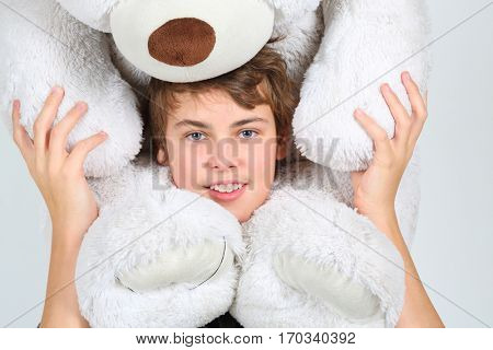 Boy teenager in grey poses with large white toy bear in studio
