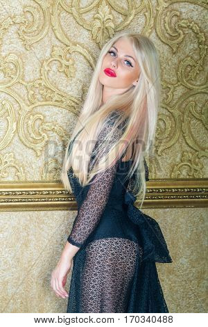 Beautiful blonde in transparent black lace dress poses near gilted wall in room