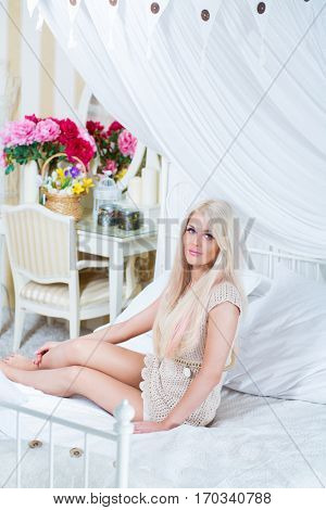 Attractive blonde sits on white bed with pillows in cozy bedroom