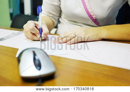 Hands of woman doctor writing description of ECG on wooden table