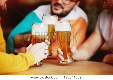 Clinking Beer Glasses in Irish Pub