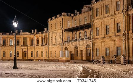 Gatchina Palace. Entrance to the right wing. Night Photography. Left elegant street lamp. Right - striped booth palace guard. Russia.