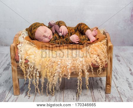 sleeping newborn boy in hat and suit on little bed with fluffy blanket