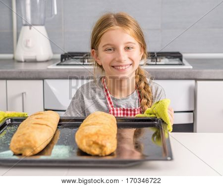 beautiful smiling litte girl with baked apple strudel on table in kitchen