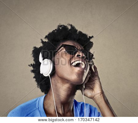 Black girl listening to music and singing loudly with passion