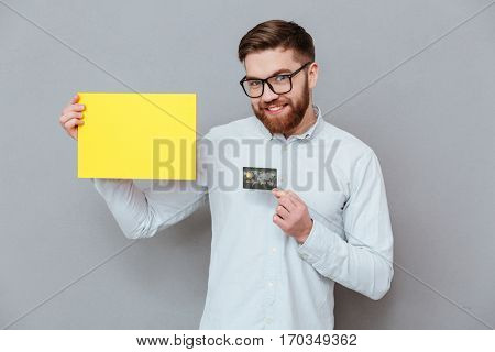 Image of attractive young bearded businessman holding copyspace blank and debit card standing over grey background.