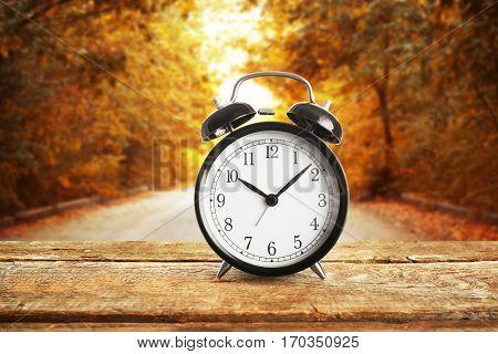 Alarm clock on wooden table against landscape background. Time change concept