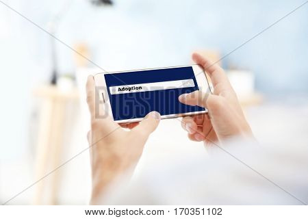 Adoption concept. Male hands with smartphone and search box on screen