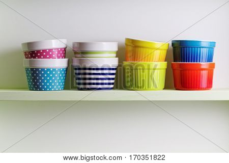 Colorful bowls on a kitchen shelf. A kitchen shelf unit holding striped and spotted bowls. Kitchen shelf arrangement.
