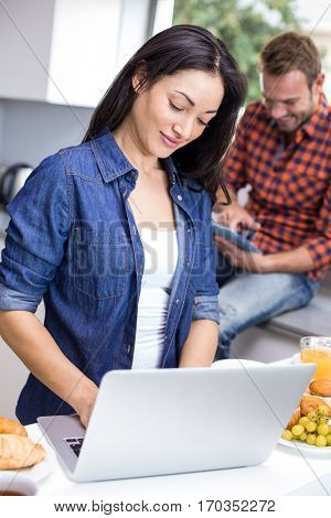 Couple using laptop and digital tablet in the kitchen during breakfast