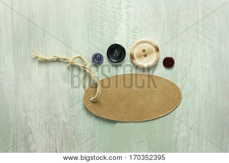 A photo of a kraft cardboard tag with a piece of twine, with retro buttons, shot from above on a light wooden board texture, with copy space