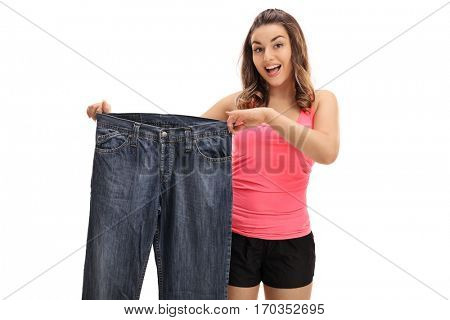 Happy young woman holding a pair of oversized jeans isolated on white background